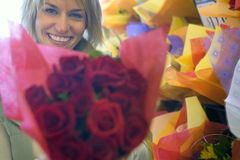 Woman holding large bouquet of red roses beside shop display in florists, smiling, close-up, portrait stock photos