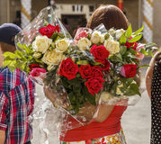 A woman holding a large bouquet of roses (back view) Royalty Free Stock Photos