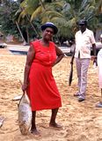Woman holding large fish on the beach. Local woman holding a large fish from the days catch on Castara beach, Tobago, Trinidad and Tobago, Caribbean stock photo