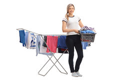 Woman holding laundry basket in front of clothing rack dryer. Full length portrait of a young woman holding a laundry basket in front of a clothing rack dryer Stock Images