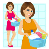 Woman holding a laundry basket full of dirty clothes Stock Photos