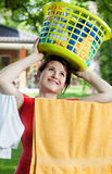 Woman holding laundry basket on her head Stock Images
