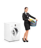 Woman holding a laundry basket next to a machine Stock Image