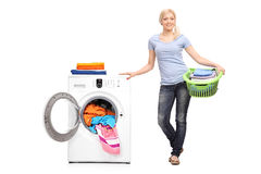 Woman holding laundry basket by a washing machine. Full length portrait of a young woman holding a laundry basket full of folded clothes and posing next to a Royalty Free Stock Images