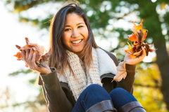 Woman holding leaves in autumn Stock Photos