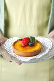 A woman holding a lemon tart with berries Stock Photo