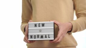 Woman holding lightbox with new normal text. post quarantine life, the end of covid-19 lockdown