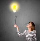 Woman holding a lightbulb balloon Stock Photos