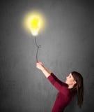 Woman holding a lightbulb balloon Stock Photos