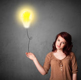 Woman holding a lightbulb balloon Royalty Free Stock Images