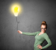 Woman holding a lightbulb balloon Stock Photography