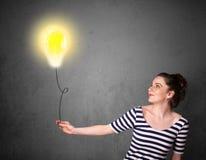 Woman holding a lightbulb balloon Stock Photo