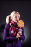 Woman holding lollypop. Young blond woman holding lollypop Royalty Free Stock Photography