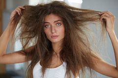 Woman With Holding Long Damaged Dry Hair. Hair Damage, Haircare. Damaged Hair. Beautiful Sad Young Woman With Long Disheveled Hair. Closeup Portrait Of Female Stock Photography