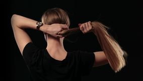 Woman holding long hair and pulling blond hair Stock Photo
