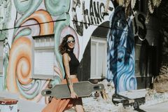 Woman Holding a Longboard While Smiling Royalty Free Stock Photos