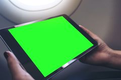 A woman holding and looking at black tablet pc with blank green desktop screen next to an airplane window. Mockup image of a woman holding and looking at black stock photo