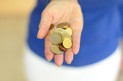 Woman holding loose change in her hand. With an assortment of Euro coins as she prepares to make a money payment Stock Photos