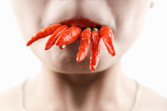 Woman holding lot of red chilies with mouth Royalty Free Stock Photos