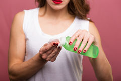 Woman holding a lotion and a cotton pad Royalty Free Stock Images