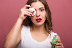 Woman holding a lotion and a cotton pad Stock Images