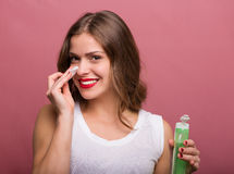 Woman holding a lotion and a cotton pad Royalty Free Stock Image