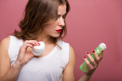 Woman holding a lotiona and a cotton pad Royalty Free Stock Photos