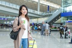 Woman holding luggage and coffee in hong kong international airp Royalty Free Stock Image