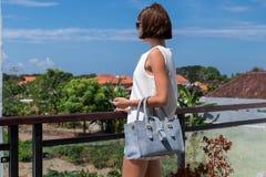 Woman holding luxury snakeskin python handbag. Bali island. Fashion bag concept on a tropical island. Royalty Free Stock Images
