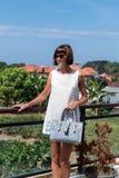 Woman holding luxury snakeskin python handbag. Bali island. Fashion bag concept on a tropical island. Stock Photos