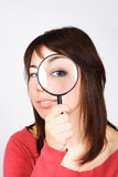 Woman holding magnifier and looking through it Royalty Free Stock Photography