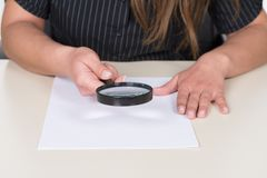 Woman is holding a magnifier over a document Royalty Free Stock Image