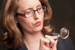 Woman holding magnifying glass Royalty Free Stock Photos