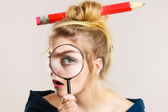 Woman holding magnifying glass having hair pencil Royalty Free Stock Photos