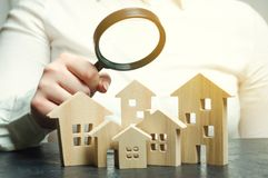 A woman is holding a magnifying glass over a wooden houses. Real estate appraiser. Property valuation / appraisal. Find a house. Search for housing. Real stock photography