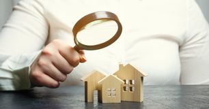 A woman is holding a magnifying glass over a wooden houses. Real estate appraiser. Property valuation / appraisal. Find a house. Search for housing. Real royalty free stock photography