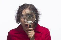 Woman holding magnifying glass up to her eye, horizontal Royalty Free Stock Photos