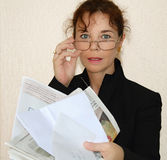 Woman holding mail. Portrait of middle age woman looking over eyeglasses as she holds mail Royalty Free Stock Image