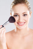 Woman holding makeup brush Stock Images