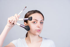 Woman Holding Makeup Brushes in Different Sizes Royalty Free Stock Photography