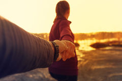 Woman holding male hand, walking in park at sunset. Follow me - woman holding male hand, walking in park at sunset time Royalty Free Stock Photos