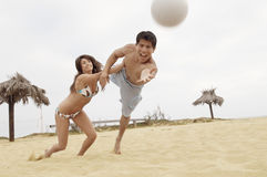 Woman Holding Man Back From Diving For Volleyball Stock Photo