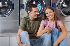 Woman Holding Man's Hand At Laundromat. Portrait of happy young women holding man's hand while sitting at laundromat royalty free stock images