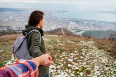 Woman holding man's hand and leading him on nature. Young traveler woman holding man's hand and leading him on nature outdoor. Couple in love Stock Photo