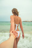 Woman holding man's hand and leads to the sea. Stock Photo