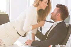 Woman  holding man`s tie in the office Stock Photography