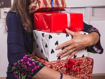Woman holding many gift boxes. Hands full. Giving a gifts. A woman holding many gift boxes in her hands. Teacher or mother`s day concept royalty free stock photos
