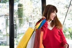 Woman holding many shopping bags. shopaholic, sale, consumerism. Asian woman holding many shopping bags. shopaholic, sale, consumerism and people concept Royalty Free Stock Images