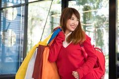 Woman holding many shopping bags. shopaholic, sale, consumerism. Asian woman holding many shopping bags. shopaholic, sale, consumerism and people concept Royalty Free Stock Image