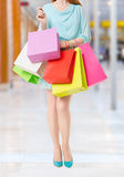 Woman holding many shopping bags in shopping mall Royalty Free Stock Photo